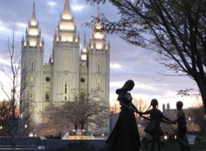 A statue of a mother with her children in front of the Salt Lake City LDS Temple.