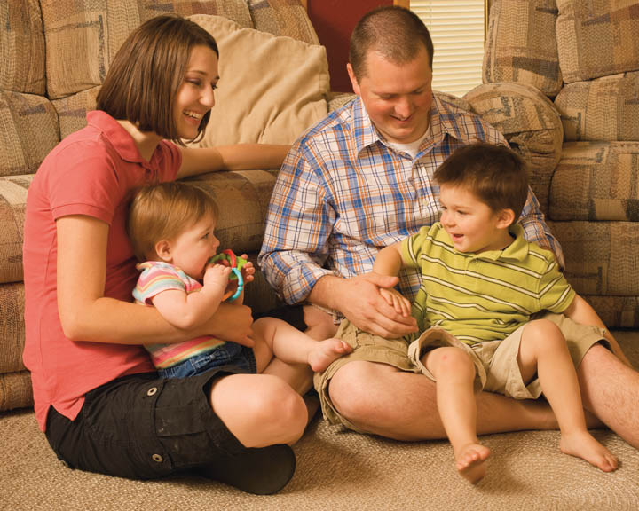 A photo of a Mormon family in their home; consists of a father, a mother, and young children.