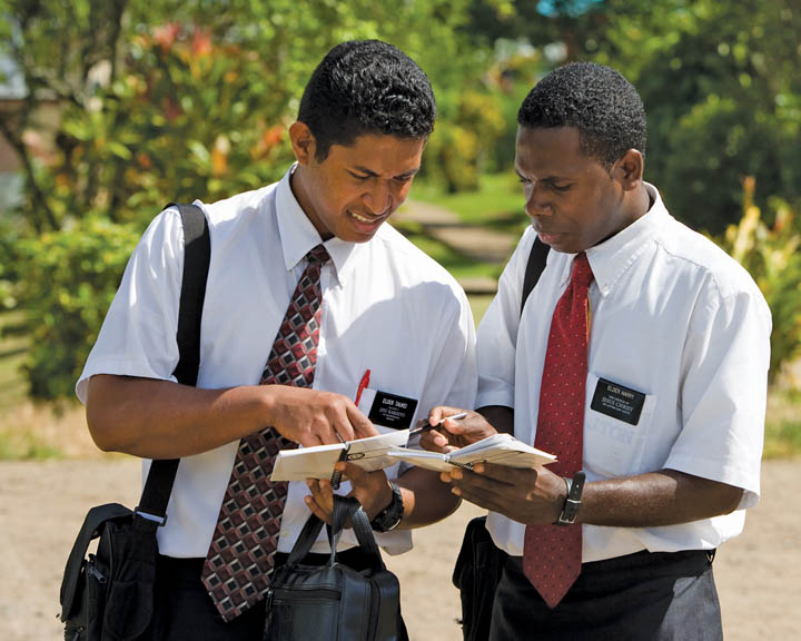 A photo of two elder missionaries reviewing their planners together.