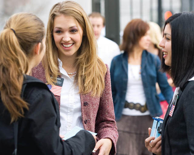 A photo of two Mormon sister missionaries teaching someone in the street.