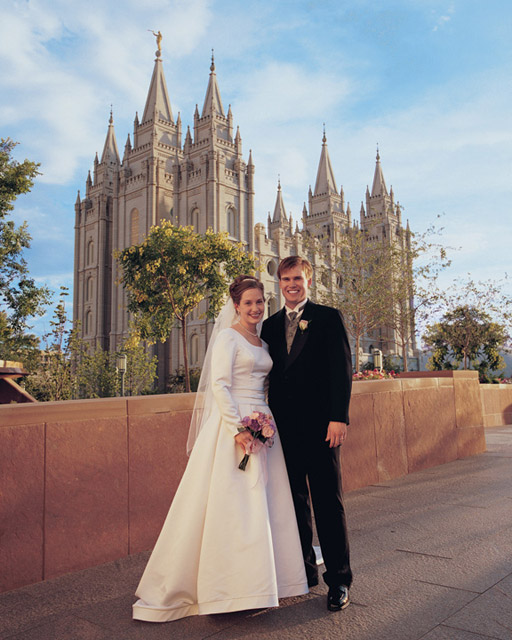 A photo of a couple standing in front of the Salt Lake City Temple after being married.