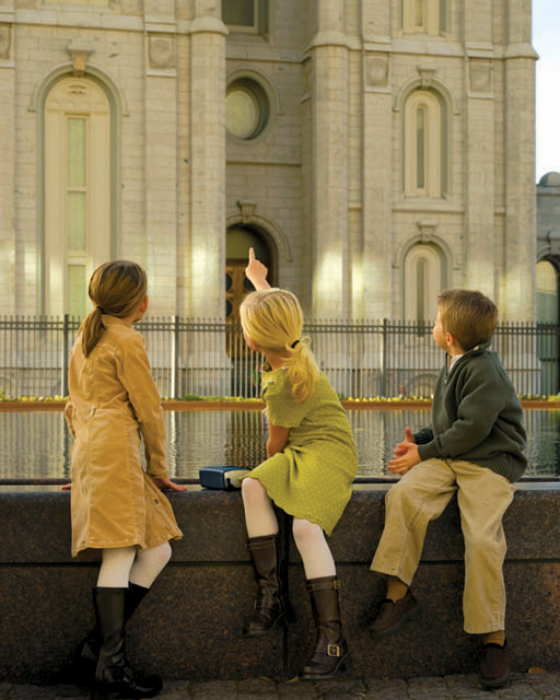 A photo of young children in Sunday clothes looking and pointing at the temple.