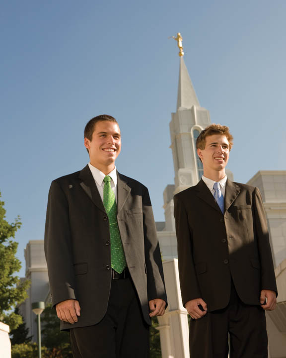 A photo of two young men in suits outside of a Mormon Temple.