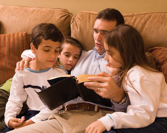 A Mormon family reading the scriptures together on a couch.