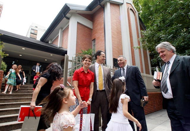 A photo of a Mormon congregation exiting the church building after a service.
