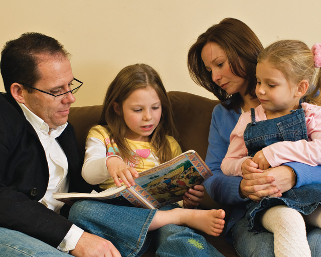 A photo of a Mormon family reading together on a couch.