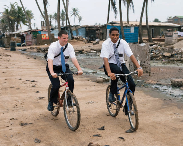 A photo of two elder missionaries riding their bikes on a dirt road.