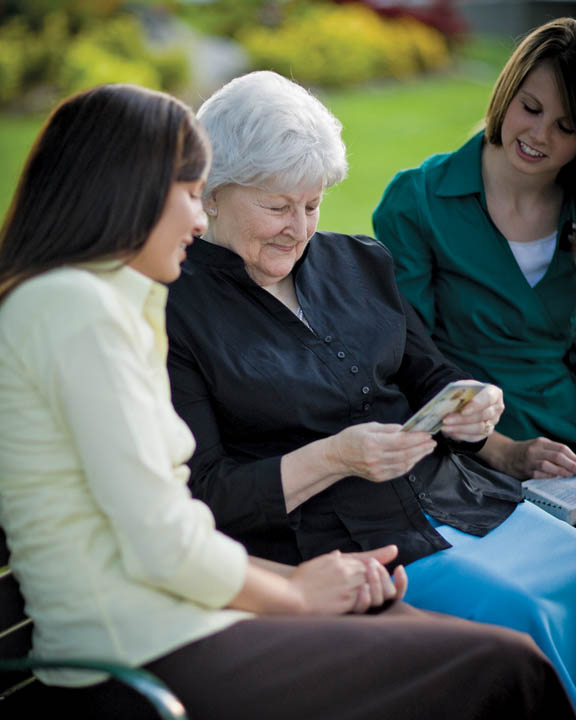 A photo of two Mormon sister missionaries speaking with a woman on a bench.