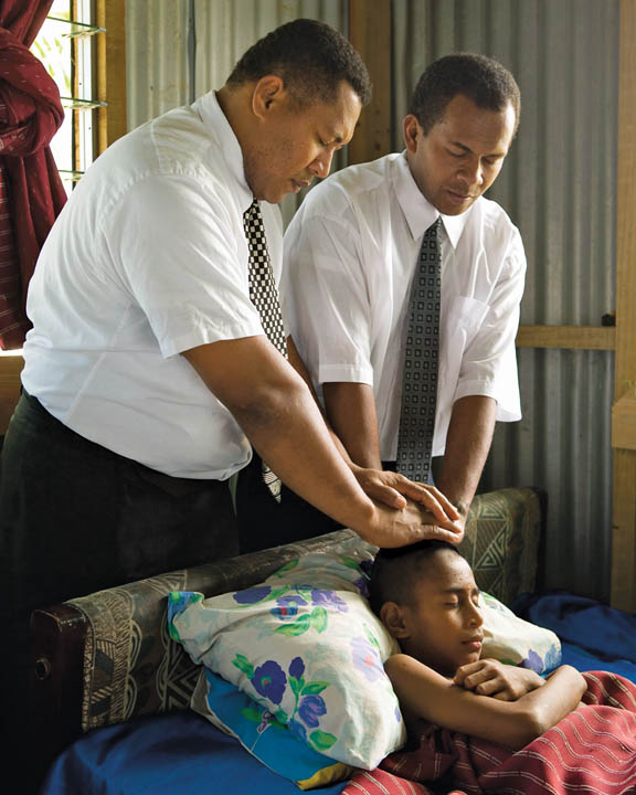 Two Mormons giving a Priesthood blessing to a young sick boy.