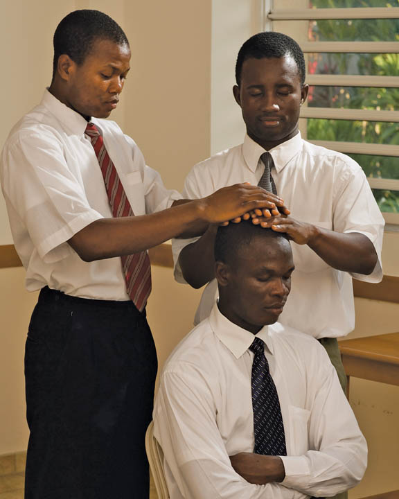 A photo of two African-American men giving the Priesthood to another African-American man.