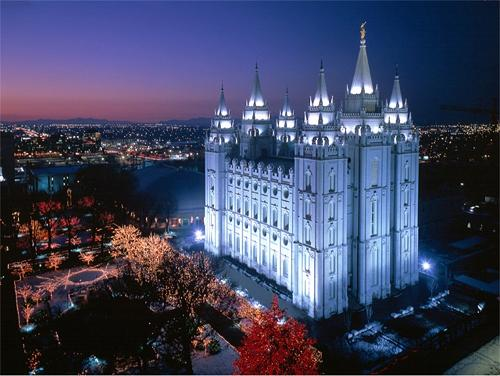 A photo of the Mormon Salt Lake City Temple at night with lights on the trees surrounding it.