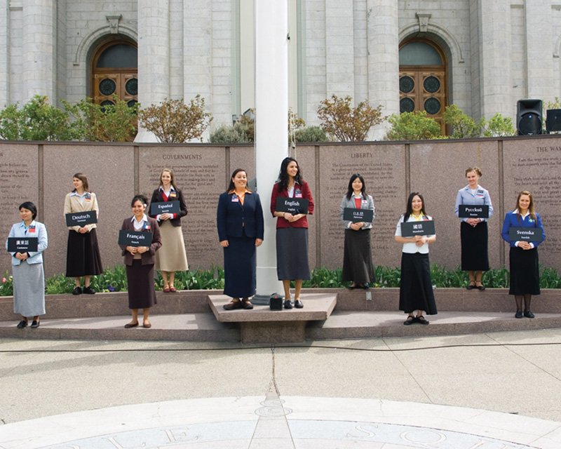 A photo of ten sister missionaries with name badges and signs indicating which language they can speak, standing in front of the Salt Lake Temple, ready to answer questions of passerby's.