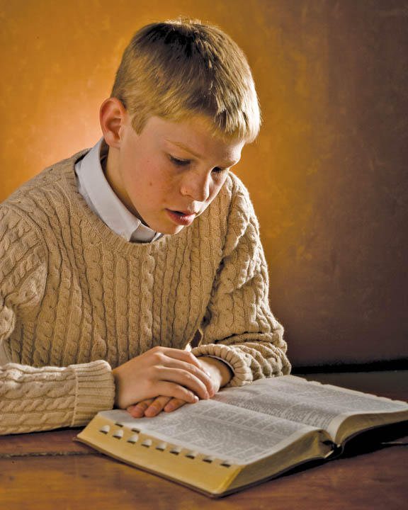 A photo of a Mormon teenage boy studying the scriptures at a table.