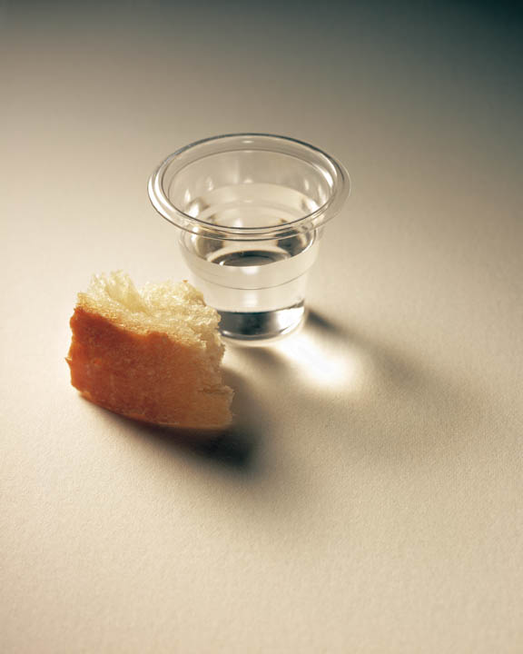 A photo of a sacrament cup of water and a piece of sacrament bread.