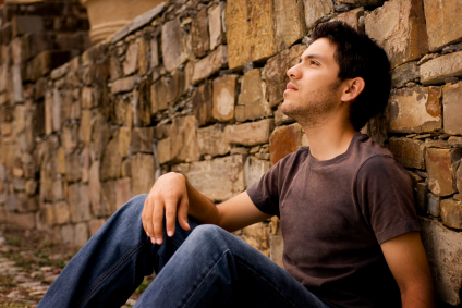 A photo of a young man thinking while he sits with his back against a rock wall.