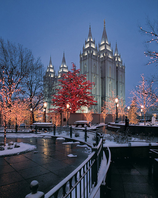 A photo of the Salt Lake City Mormon Temple at dusk with snow all around.