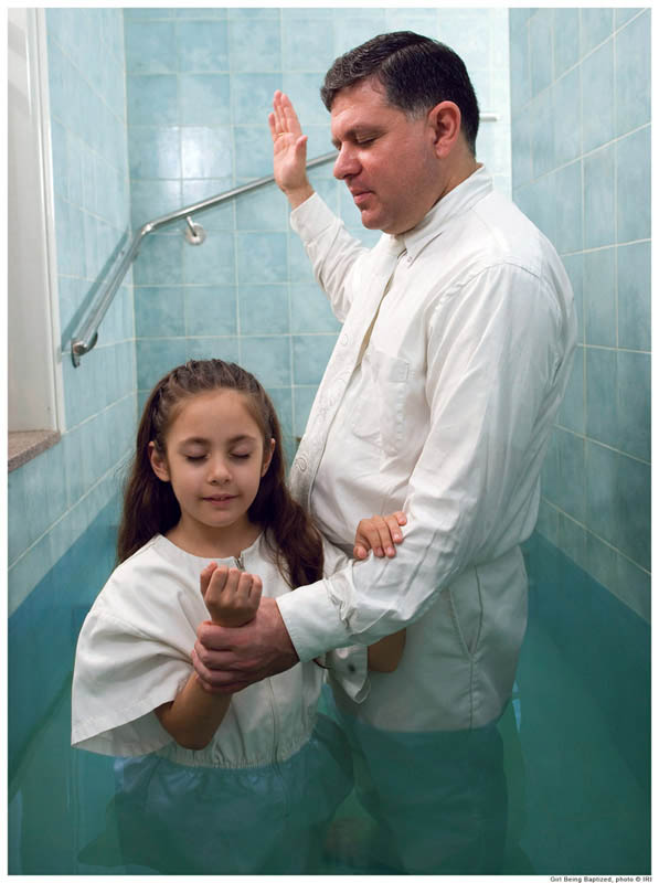 A photo of a young girl being baptized into the Mormon church by her father.