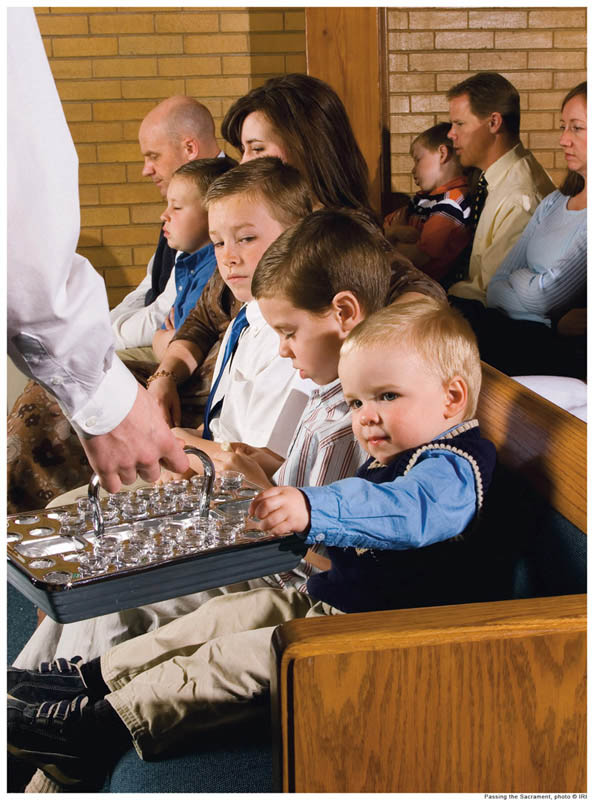 A photo of a young man passing the sacrament to a young family at a Mormon church.