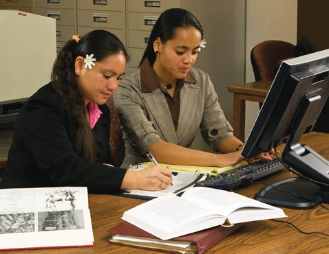 A photo of two Mormon women doing family history together on a computer.