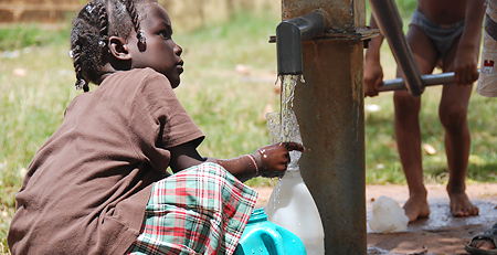 A photo of a young child gathering water during a Mormon humanitarian aid clean water project.