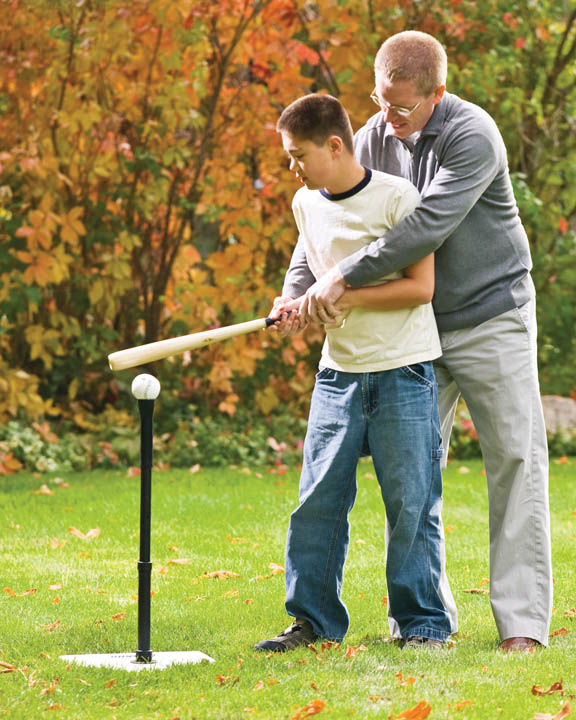 A photo of a father teaching his son how to swing a baseball bat.