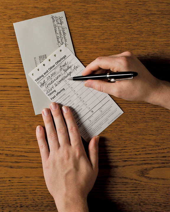 A close-up photo of a Mormon filling out a tithing slip.