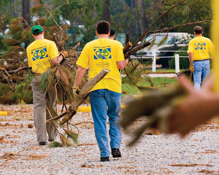 A photo of a few Mormon men helping clear branches as part of a Helping Hands service project.