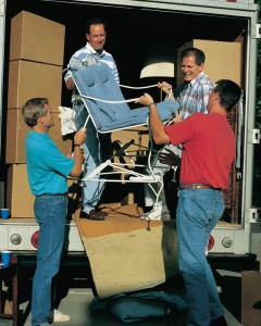 A photo of several Mormon men helping unload a moving truck for someone.