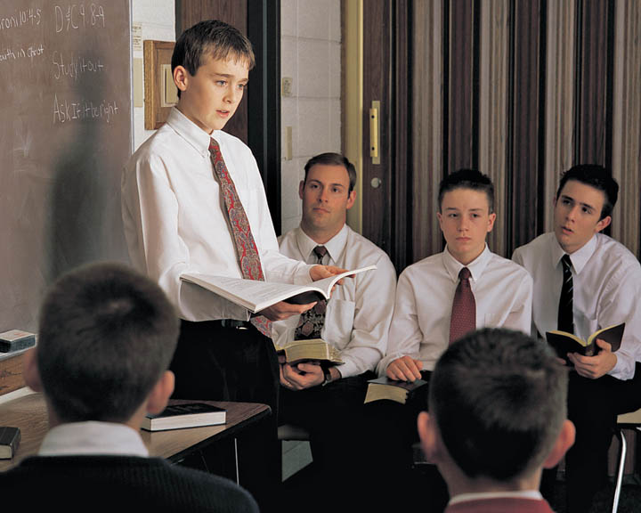 A photo of a young man who holds the Aaronic Priesthood teaching a class in a Mormon church.