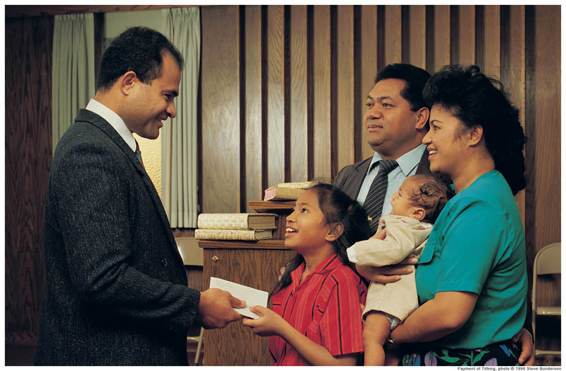 A photo of a family handing tithing to their bishop.