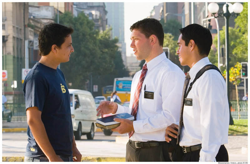 Mormon missionaries talk to a young man.