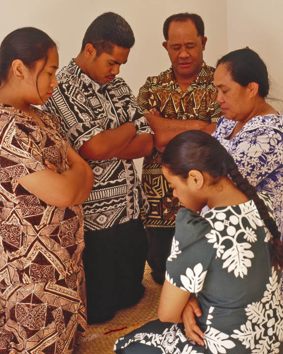 A photo of a Polynesian Mormon Family kneeling down together in prayer.