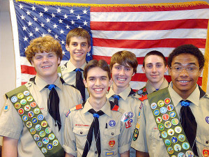 A photo of six boy scouts in their uniforms, standing in front of the American flag.