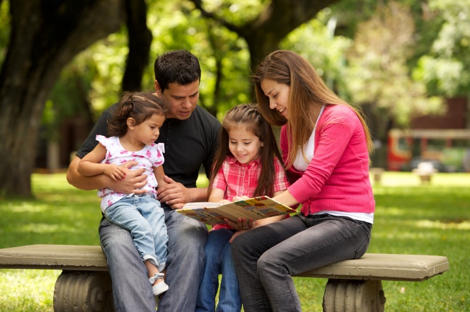 Parents reading to children at a park.