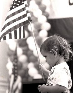 Little girl waving an American flag during a political rally.