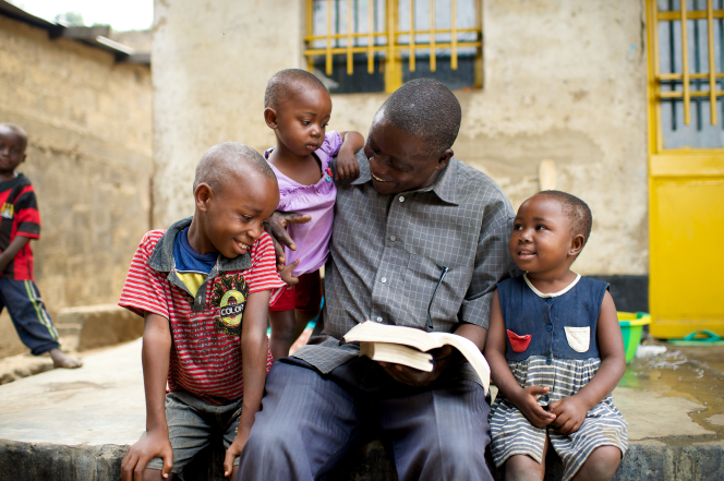 Father studying scriptures with his children