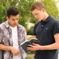 Young men reading the Book of Mormon