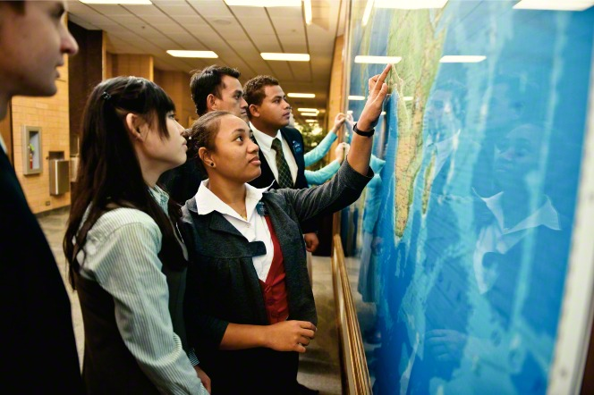 Mormon missionaries look at a map of the world