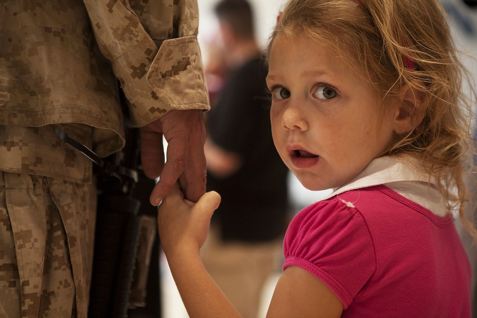 A little girls hold the hand of her parent, who is a soldier.