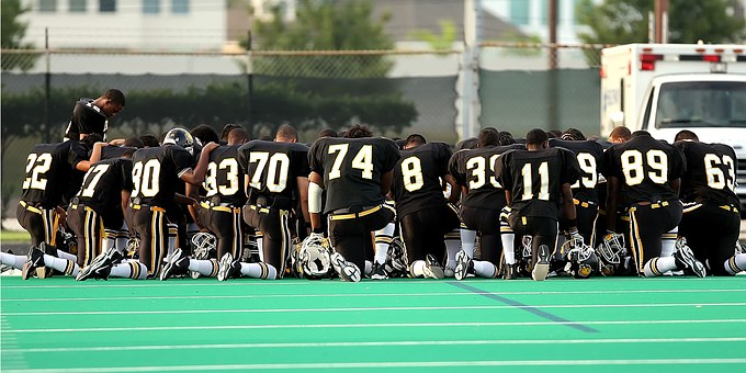 Football players kneel down and pray.
