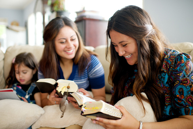 A mother studies the scriptures with her daughters.