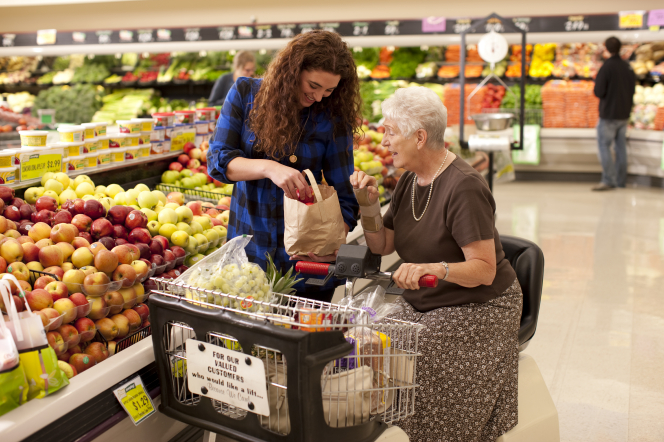 A woman helps an elderly woman shop for fruit at a grocery store.