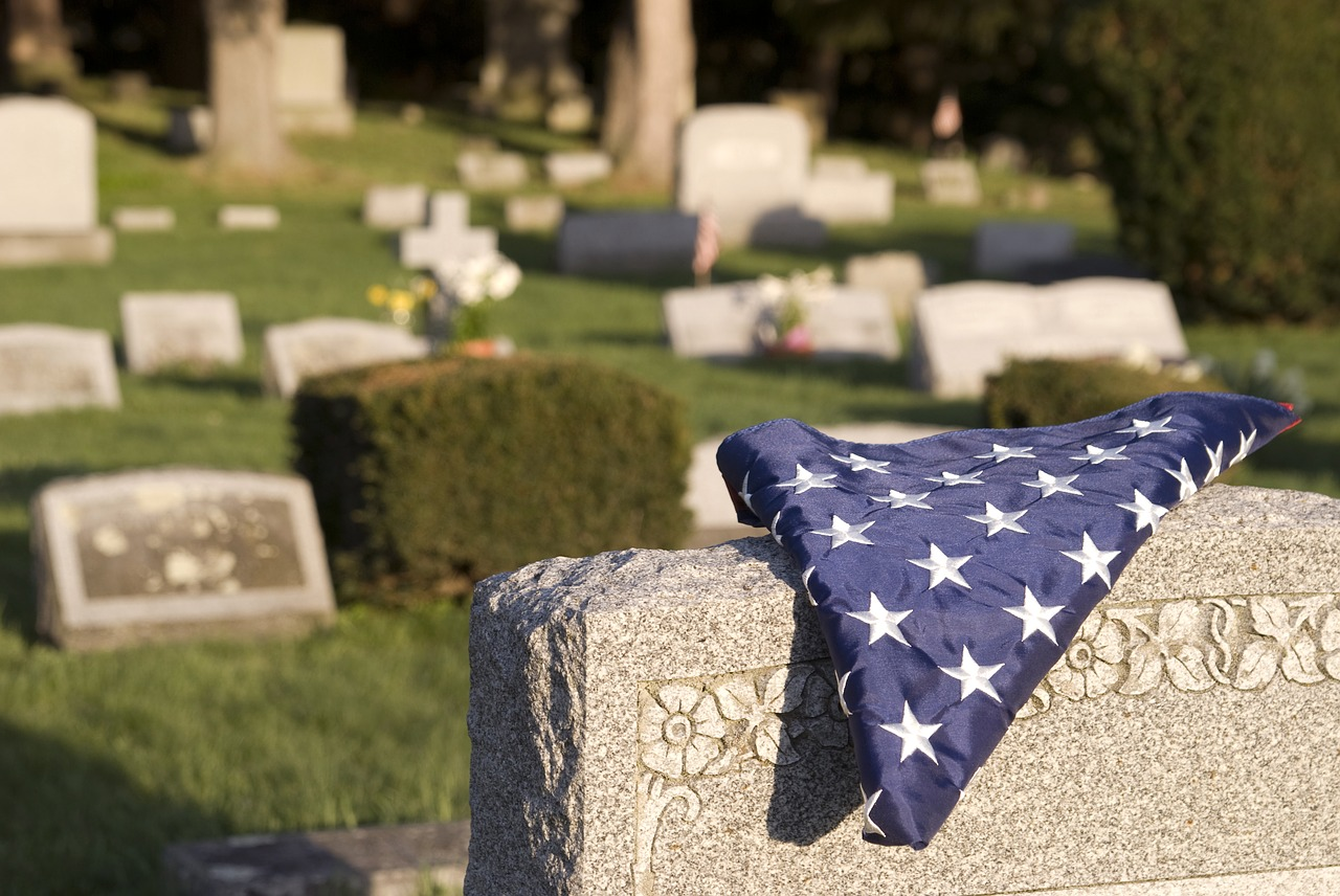 An American flag on a headstone reminds us of the sacrifice and service made by our veterans.