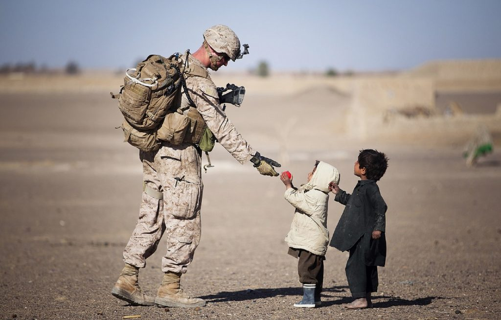 An American soldier interacts with young children.