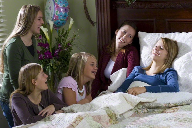 Young women visit a sick friend. Youth can share their love for others in the ministering program of The Church of Jesus Christ of Latter-day Saints.