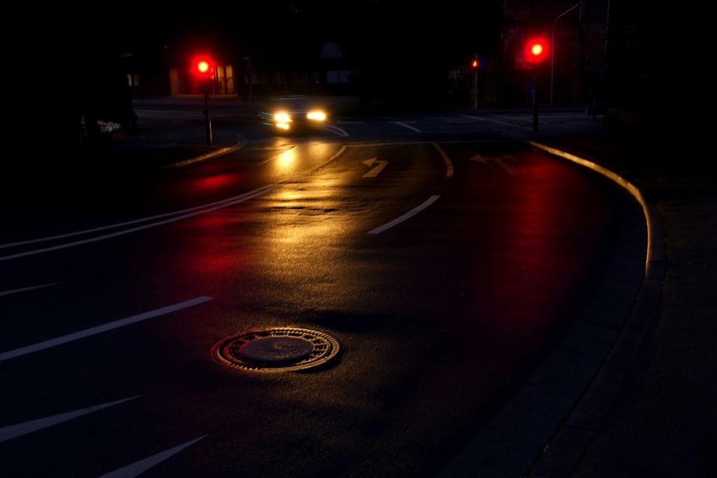 A car stops at a red light at night. Stoplights can be a blessing or a burden, just like God's commandments.