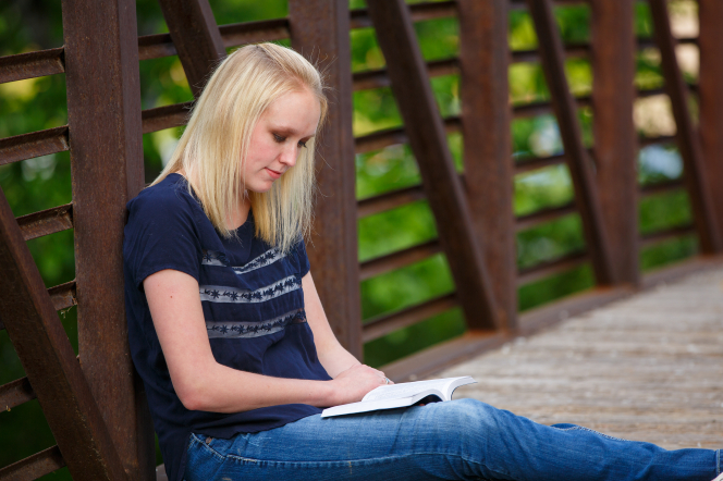 A young woman reads the Book of Mormon.