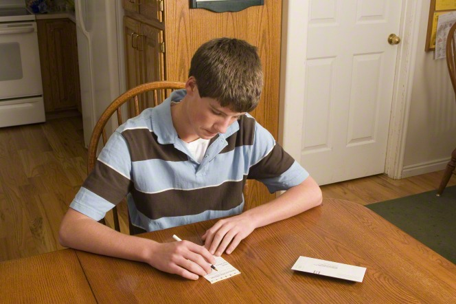 A young man fills out a tithing slip.