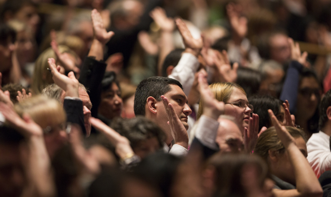 Members of The Church of Jesus Christ of Latter-day Saints raise their hands to sustain their leaders in the Saturday session of General Conference.
