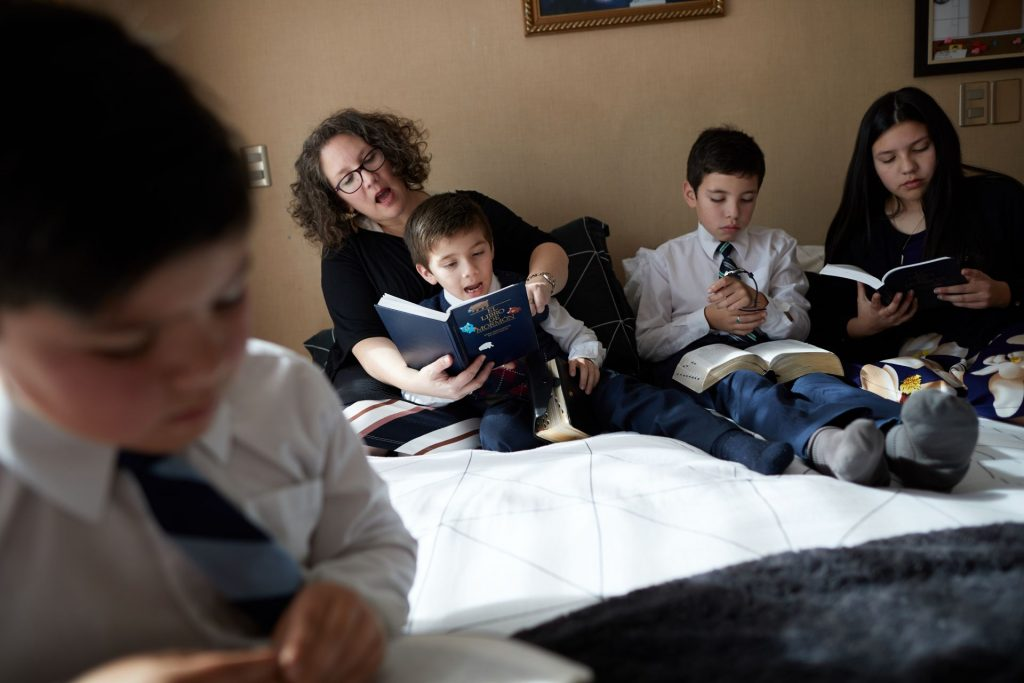 A family studies the scriptures at home.